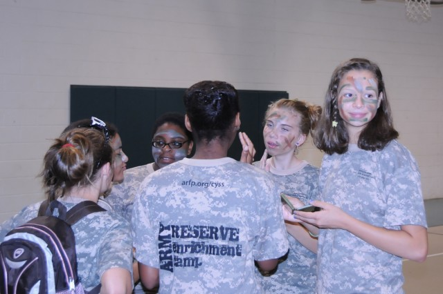Military and non-military children staying at the YMCA Camp Hanes in King, N.C. apply face paint during Military Day activities on July 11. The week-long camp included the Military Day where children were exposed to different aspects of military life such as, Army heater meals, camoflauge face paint, physical training and a static vehicle display. The children also wrote supportive letters to veterans and drew pictures that will become parts of a larger mural as a part of Project S.N.A.P. and the Operation Grateful Nation Mosaic Mural project.
