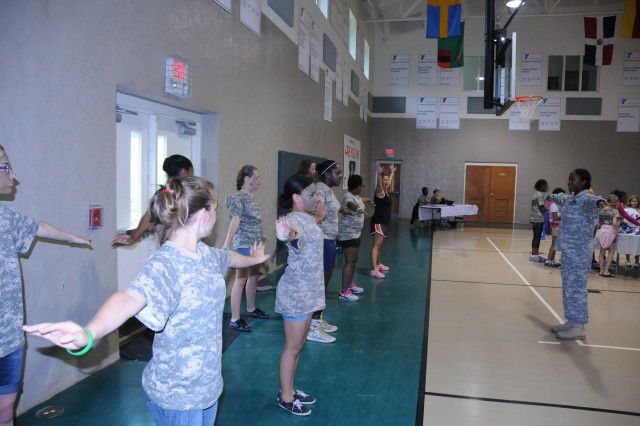 Led by Sgt. Jolanda Howard of the 108th Training Command out of Charlotte, N.C., military and non-military children staying at the YMCA Camp Hanes in King, N.C. do some physical fitness training during Military Day activities on July 11. The week-long camp included the Military Day where children were exposed to different aspects of military life such as, rmy heater meals, camoflauge face paint, physical training and a static vehicle display. The children also wrote supportive letters to veterans and drew pictures that will become parts of a larger mural as a part of Project S.N.A.P. and the Operation Grateful Nation Mosaic Mural project.