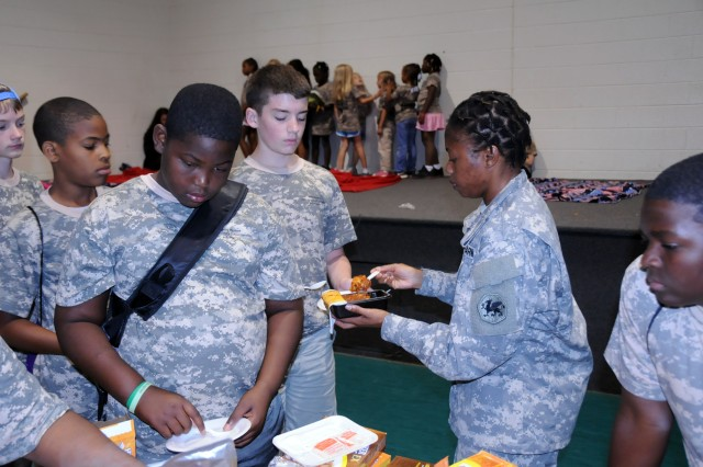 Staff Sgt. Eileen Payne of the 108th Training Command distributes the Army Heater Meal version of lasagna to some children at Camp Hanes, N.C. during Military Day activities on July 11. The week-long camp included a Military Day where children were exposed to different aspects of military life such as, camoflauge face paint, physical training and a static vehicle display. The children also wrote supportive letters to veterans and drew pictures that will become parts of a larger mural as a part of Project S.N.A.P. and the Operation Grateful Nation Mosaic Mural project.