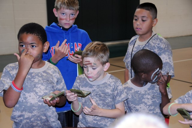 Military and non-military children staying at the YMCA Camp Hanes in King, N.C. apply face paint during Military Day activities on July 11. The week-long camp included the Military Day where children were exposed to different aspects of military life such as, camoflauge face paint, physical training and a static vehicle display. The children also wrote supportive letters to veterans and drew pictures that will become parts of a larger mural as a part of Project S.N.A.P. and the Operation Grateful Nation Mosaic Mural project.
