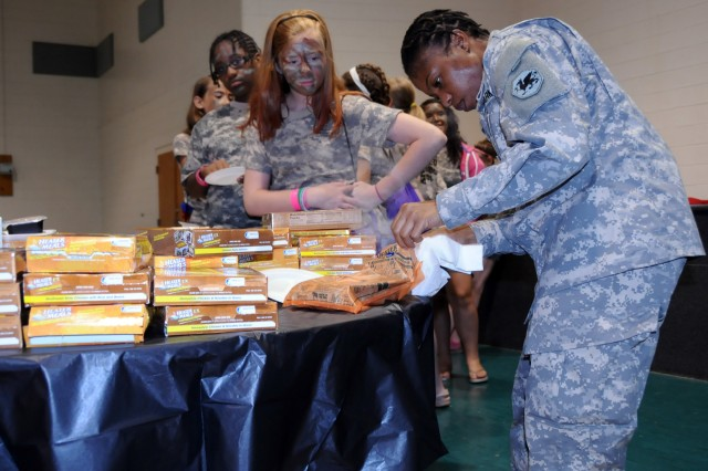 Staff Sgt. Eileen Payne of the 108th Training Command show some children at Camp Hanes, N.C. how to prepare heater meals during Military Day activities on July 11. The week-long camp included a Military Day where children were exposed to different aspects of military life such as, camoflauge face paint, physical training and a static vehicle display. The children also wrote supportive letters to veterans and drew pictures that will become parts of a larger mural as a part of Project S.N.A.P. and the Operation Grateful Nation Mosaic Mural project.