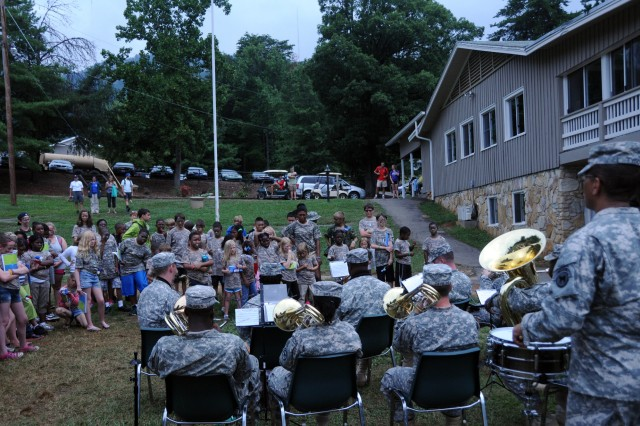 Soldiers of the 208th Army Band entertain military children at Camp Hanes in King, N.C. on July 11. The week-long camp included a Military Day where children were exposed to different aspects of military life such as, camoflauge face paint, physical training and a static vehicle display. The children also wrote supportive letters to veterans and drew pictures that will become parts of a larger mural as a part of Project S.N.A.P. and the Operation Grateful Nation Mosaic Mural project.