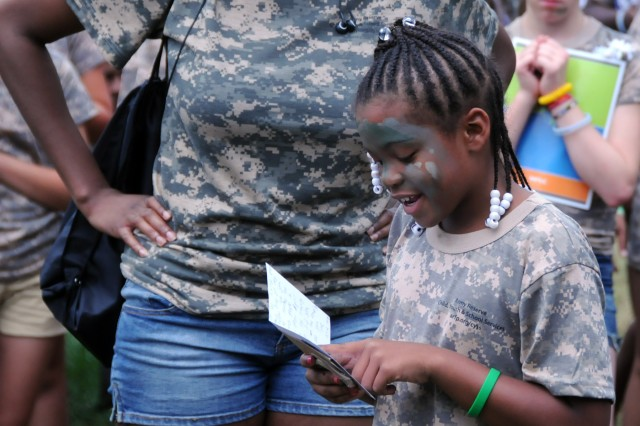 Aleira Artis, a military child at Camp Hanes in King N.C., reads a letter to Soldiers that she wrote on Miliary Day, July 11. The week-long camp included the Military Day where children were exposed to different aspects of military life such as, camoflauge face paint, physical training and a static vehicle display. The children also wrote supportive letters to veterans and drew pictures that will become parts of a larger mural as a part of Project S.N.A.P. and the Operation Grateful Nation Mosaic Mural project. In Aleira's letter she thanked the Soldiers present, members of the 108th Training Command, the 208th Army Band and the 81st Regional Support Command, as well as promising to become a Soldier herself when she grows up.