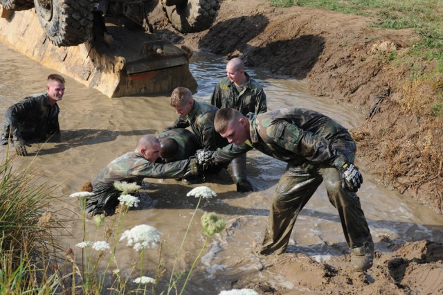 "Marines help each other out of the restraining mud pit after successfully recovering the Buffalo Mine Resistant Ambush Protected Vehicle "" and flipping it back over for the next group "" as part of the Vehicle Recovery Course"