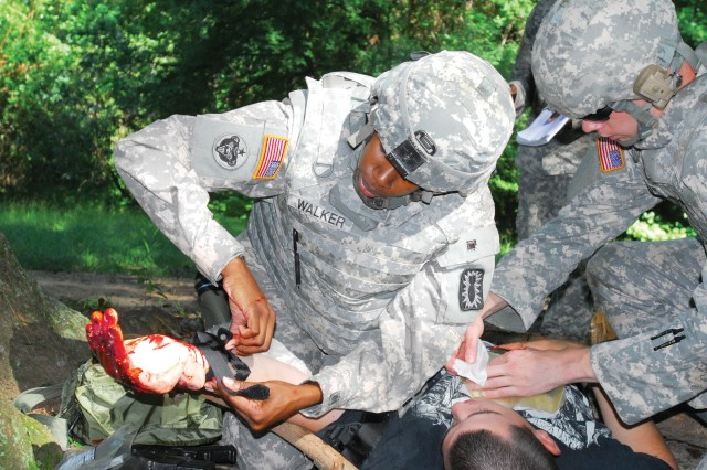 "Staff Sgt. Camille Walker applies a tourniquet to a ""victim"" Wednesday. The simulated event was a graded test for Soldiers taking the Combat Lifesaver Course."