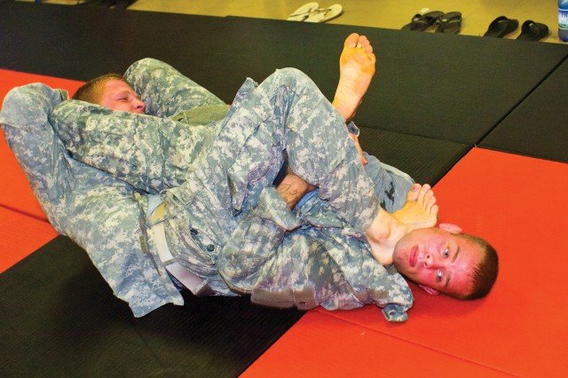 Andrew McLauchlan, right, practices with a teammate Wednesday at Matt Larsen's Fitness Center. He will be one of 24 (16 champions and eight alternates) Soldiers from the 3rd Infantry Division competing in the U.S. Army Combatives Championship at Fort Hood, Texas, July 25-28, 2012.