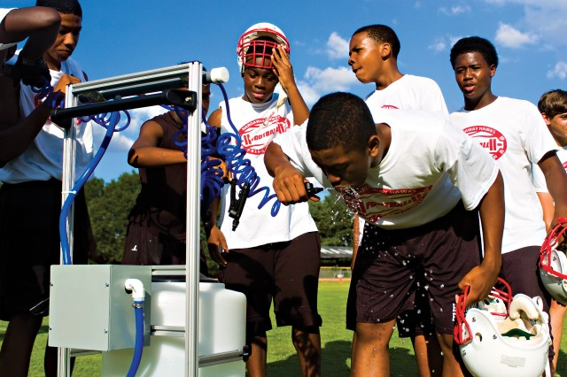 Players from the Hardaway football team take a water break July 10 at the school's practice field. Hardaway hosted a multi-team practice that also included Chattahoochee County and Shaw. The practice was held at 6 p.m. in order to be in compliance with the new Georgia High School Association heat policy. The policy does not allow teams to practice outdoors when the Wet Bulb Globe Temperature Index reading is 92 or higher.
