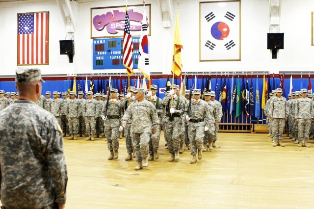 "At Camp Red Cloud in Uijeongbu July 13, a color guard takes position during a ceremony in which Col. John M. Scott assumed command of the U.S. Army Garrison Red Cloud and Area I, replacing Col. Hank Dodge, who moves to a new assignment. Command Sgt. Maj. Michael Hatfield became the garrison's new top senior enlisted leader, replacing Command Sgt. Maj. Nidal Saeed, who is retiring after 28 years in the Army. The 2nd Infantry Division Band provided music for the ceremony, which was held inside the Camp Red Cloud Fitness Center. At the head of the color guard is Lt. Col. Steven G. Finley, (center) commander, U.S. Army Garrison Casey. "" U.S. Army photo by Sgt. First Class Jeff Troth"