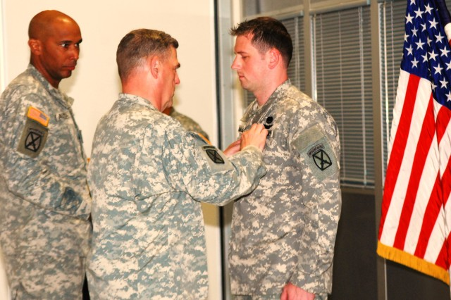 Maj. Gen. Mark A. Milley, Fort Drum and 10th Mountain Division commander, pins the Distinguished Flying Cross to the uniform of Staff Sgt. Brian D. Cammack during a ceremony June 29 at Wheeler-Sack Army Airfield, as Col. Pedro Almeida, 10th Combat Aviation Brigade commander, looks on. Cammack, a flight medic, earned the prestigious award by treating and extracting from the battlefield six wounded American Soldiers and three Americans killed in action March 29, 2011, in eastern Afghanistan.