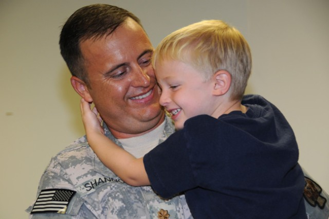 Maj. Mike Shannon, 164th TAOG operations officer, holds his son, Sammy, at Cairns Army Airfield July 14 before he deploys with his unit to Kuwait.