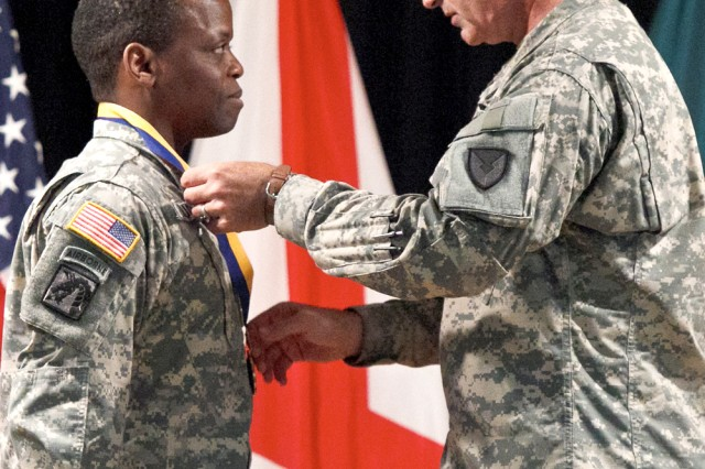 Col. Darryl J. Briggs, CMA director of Stockpile Operations, presents the U.S. Army Chemical Corps Regimental Association Order of the Dragon medal to Lt. Col. Willie J. Flucker Jr. The medal was one of the honors presented to Flucker during ANCA's Change of Responsibility July 12.