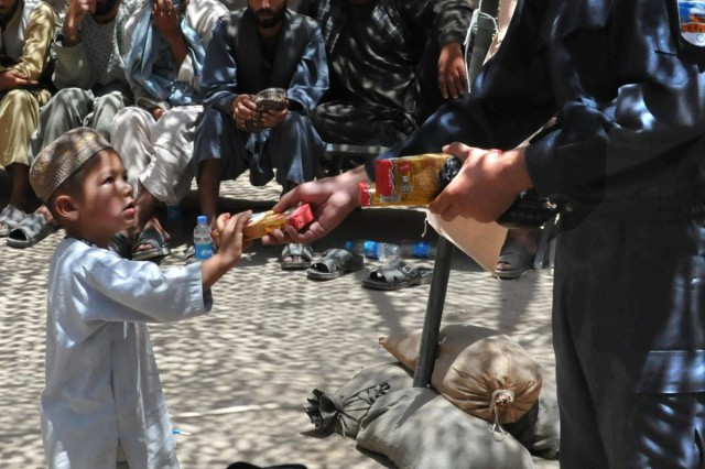 An Afghan National Police member hands out a snack to a local Afghan boy, July 7, 2012, at a shura in Tieranon, a village cluster in Zharay district. Shuras were held with the local populous to ensure the local villagers had a voice in improvements and security operations.