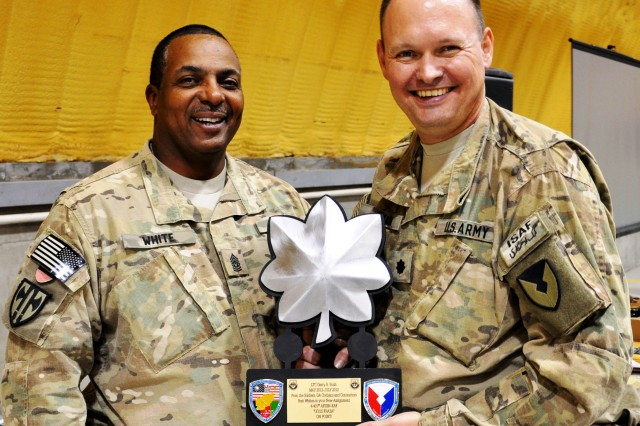 Command Sgt. Maj. Errol White, senior enlisted leader of the 4th Battalion, 401st Army Field Support Brigade presents a plaque to Lt. Col. Garry Bush, outgoing battalion commander, on July 13 at Kandahar Airfield, Afghanistan. (Photo by Sgt. Gregory Williams, 3rd SC(E) Public Affairs)