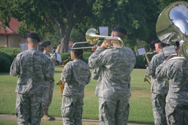 Chief Warrant Officer 4 Kathy Landas, 380th U.S. Army Band commander, conducts her band during a reveille ceremony July 9 in front of McNair Hall at Fort Sill. The Richmond, Va.-based Reserve band is at Fort Sill performing its two-weeks annual training.