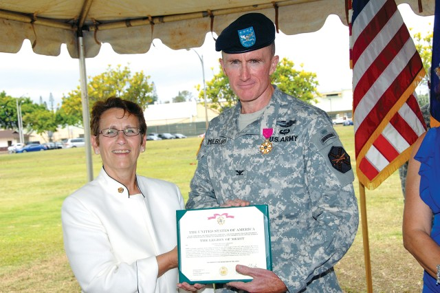 Debra Zedalis, region director, Installation Management Command-Pacific, presents the Legion of Merit to Col. Douglas Mulbury, outgoing commander, U.S. Army Garrison-Hawaii, prior to his change of command ceremony, July 17.