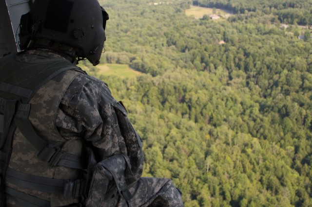 A crew member looks out from a UH-60 medevac Black Hawk helicopter from Company F, 1-169th General Support Aviation Battalion of the New York Army National Guard during medical evacuation training at Marcy, N.Y., July 12, 2012.