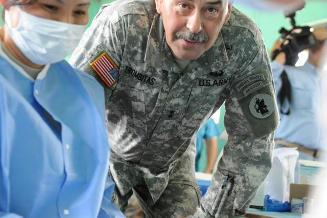 Maj. Gen. Simeon G. Trombitas, commanding general of U.S. Army South, looks in on a Guatemalan girl receiving dental treatment during a dental readiness training exercise near Pocola, Guatemala June 27.
