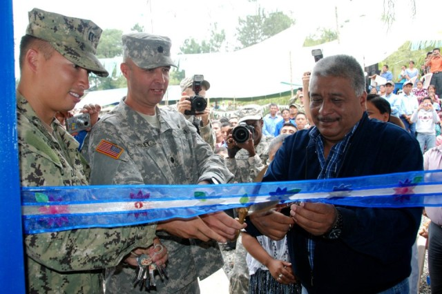 (Left to right) U.S. Navy Lt. Jeff Dong, Naval Mobile Construction Batallion 23, U.S. Army Lt. Col. John W. Findley, Beyond the Horizon 2012 Guatemala task force commander, and Julio Romeo, San Cristobal, Verapaz mayor, cut a symbolic ribbon during a ceremony at the El Rancho medical clinic near Coban, Guatemala. Construction of the clinic was part of BTH-Guatemala, a U.S. Army ...South exercise deploying military engineers and medical professionals to Guatemala for training, while providing services to rural communities.