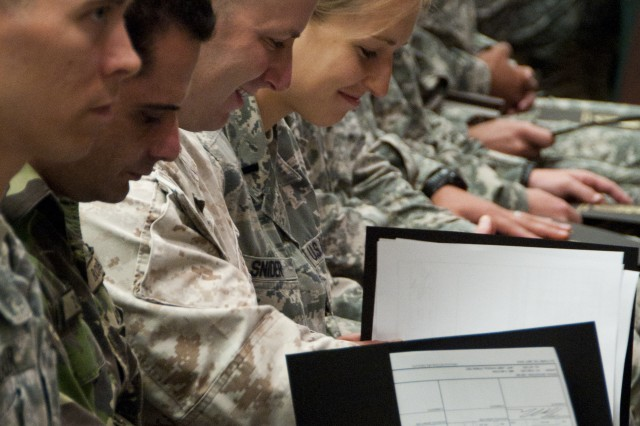 U.S. Marine Corps Capt. Daniel H. Schwartz and U.S. Air Force 1st Lt. Danielle M. Snider review their Psychological Operations Qualification Course diplomas after receiving them during the course's graduation ceremony July 20 on Fort Bragg, N.C. Although primarily filled with U.S. Army officer and noncommissioned officers, the course is also available to sister-service U.S. service members and allied-nation students. (U.S. Army photo by Dave Chace, SWCS Public Affairs Office)