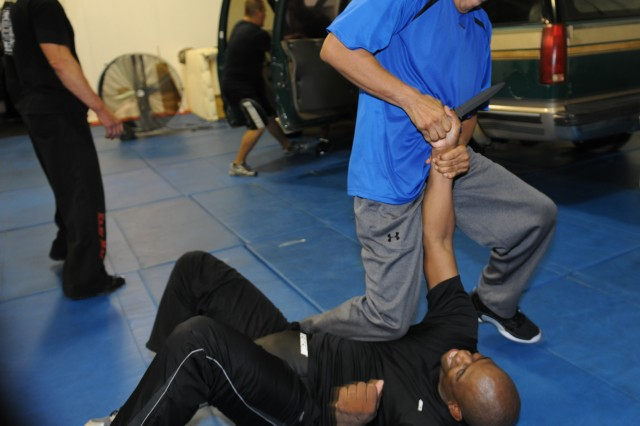"James Breaux, U.S. Army South personnel recovery, tries to take a blade from an attacking Sgt. 1st Class Kim Lofton, a chaplain assistant during a three-day captivity avoidance course at the STW Krav Maga gym in San Antonio July 16-18. Krav Maga, a Hebrew word meaning ""contact combat"", is a non-competitive defensive tactic system which teaches students how to defend against attacks from behind, while blindfolded and in confined spaces"