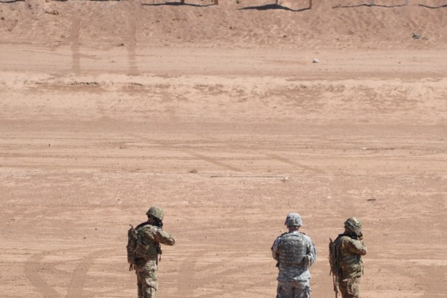 A range safety splits two Soldiers as they fire upon their respective targets from 300 m., during 1st Armored Division's first Squad Designated Marksmanship Competition at Dona Ana Base Camp, N.M., range 56, July 18.