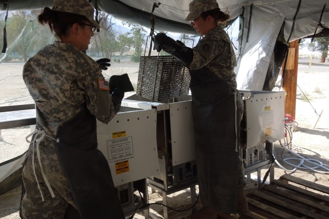 Washing dishes in the field kitchen at Hawthorne Army Depot, Nev., during Operation Golden Cargo.
