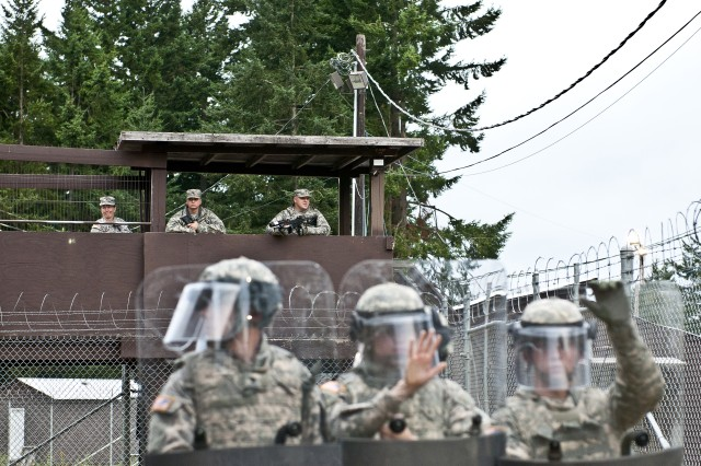Soldiers with the 67th Military Police Company, 508th MP Battalion, pull watch from above July 18 while corrections specialists with the battalion work to diffuse unrest among detainee role players during a three-day training exercise on Joint Base Lewis-McChord, Wash. The exercise tested the battalion, which hasn't trained in the field in more than two years, on its ability to run a detention camp in a deployed environment.