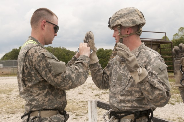 Sgt.  Jeffray C. Solter of Lafayette, Ind., checks the rappelling gloves of Spc. George Luther, of Westfield Ind., for any tears before beginning rappelling at Warrior Tower at Fort Leonard Wood, Mo., during Operation Golden Cargo, July 15, 2012.