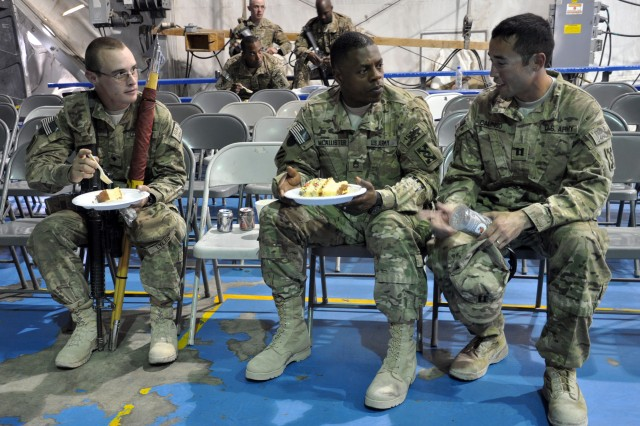 Spc. Justin Lyles, an operation specialist, 558th Movement Control Team (left), Sgt. 1st Class Joenathan Mcallister, a first sergeant, 558th MCT and Cpt. Anthony Calingo, commander, 558th MCT, eat cake after the 257th Movement Control Battalion transfer of Authority ceremony on July 18, 2012 at Bagram Airfield. The 558th MCT is one of 19 MCT's under the movement control battalions command. (U.S. Army photo by Sgt. Gregory Williams)