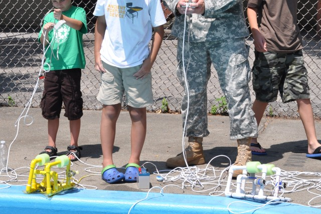 Col. Kevin Hilman, Natick Soldier Research, Development and Engineering Center military deputy, uses a remotely operated vehicle with the help of some students. Natick Soldier Research, Development and Engineering Center hosted a Land and Sea Robotics Camp for 20 middle school students assisted by 14 high school volunteers, July 9-12, 2012, and July 16-19, 2012.