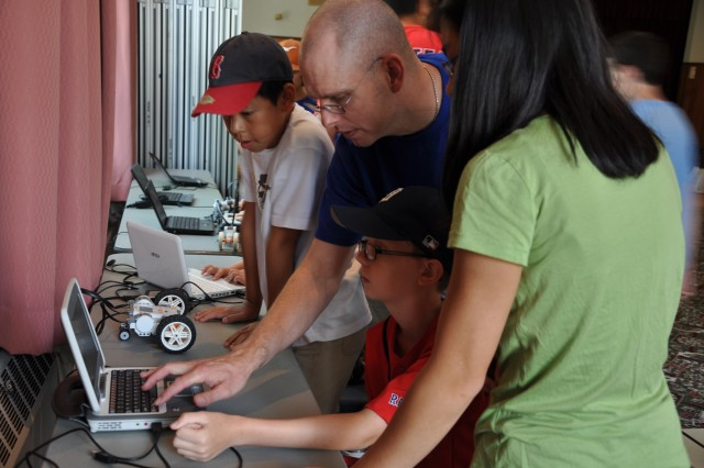 Teacher Doug Scott assists students with a computer program that links to their Lego NXT during the Land and Sea Robotics Camp at Natick Soldier Research, Development and Engineering Center, Mass. Natick Soldier Research, Development and Engineering Center hosted a Land and Sea Robotics Camp for 20 middle school students assisted by 14 high school volunteers, July 9-12, 2012, and July 16-19, 2012.