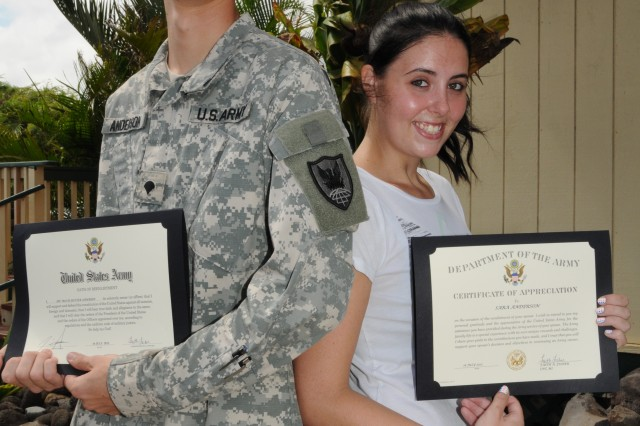 Spc. Travis Anderson, an intelligence analyst assigned to Headquarters and Headquarters Company, 311th Signal Command (Theater), and his wife Sarah show off their reenlistment oath and certificate of appreciation after Anderson reenlisted in the Army for 6 years, at Dillingham Airfield, 16 July.
