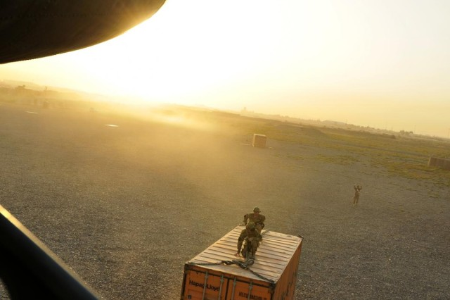A CH-47 Chinook helicopter, assigned to Company B, 1st Battalion, 111th Aviation Regiment, currently attached to 3rd Battalion, 25th Combat Aviation Brigade, lines up to sling load a container full of supplies in the early morning hours on Kandahar Airfield, Afghanistan, to take to a forward operating base as its first mission for the day July 20.
