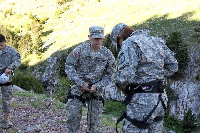 West Point Cadet John Meyer assisted Cadet Carolina Ortega, who is from the University of Colorado at Colorado Springs, with preparations for their river crossing training. Once the Cadets had been trained with their safety gear, they spotted for each other as they put the gear on and tightened it down.