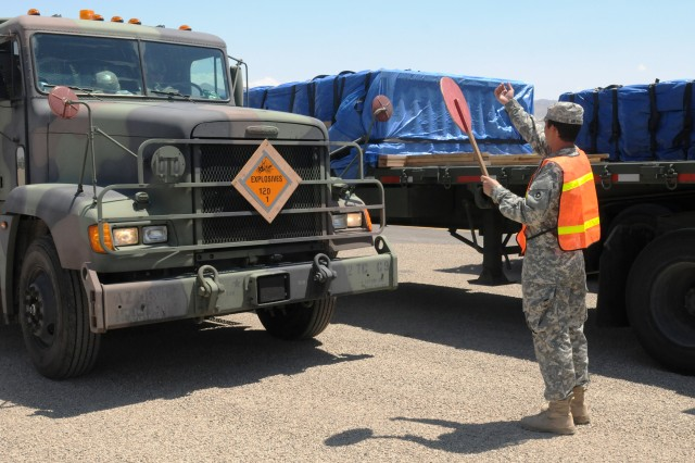 Spc. Kody R. Melendrez of Fresno, Calif., a movement specialist with the 924th Transportation Company's Trailer Transfer Point Detachment, directs trucks as they arrive July 14 at the transfer yard outside Winnemucca, Ariz. Soldiers in the Reserve unit supervised the exchange of trailers lbetween trucks during Operation Golden Cargo, an annual military mission to ship ammunition throughout the United States.