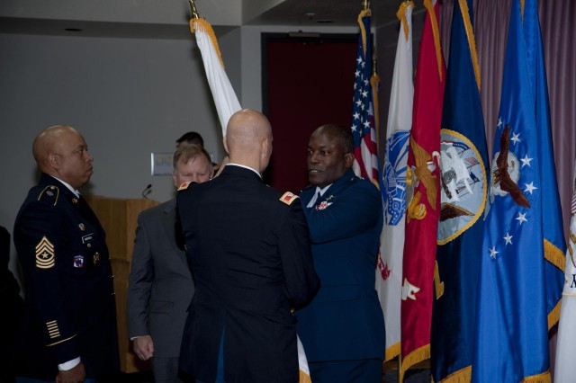 The Director of the Defense Information Systems Agency, U.S. Air Force Lt. Gen. Ronnie D. Hawkins, Jr., passes the flag, or colors of the Joint Interoperability Test Command to U.S. Army Col. Douglas J. Orsi, as Orsi assumes command of JITC, July 24. (Photo by Tim Toms)
