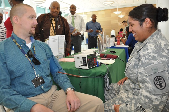 (From left) Lee Benysek of CERDEC gets his blood pressure checked by Spc. Melissa Ito of Kirk U.S. Army Health Clinic during the July 24 health fair in the Myer Auditorium at the C4ISR Center of Excellence Campus.