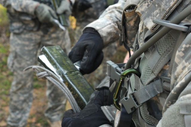 Spc. Joel Stair, assigned to 316th Mobility Augmentation Company, 844th Engineer Battalion, 926th Engineer Brigade, 412th Theater Engineer Command, cuts a block of C4 explosive before attaching a piece of detonation cord in preparation for a demolition range held during River Assault 2012, at Fort Chaffee, Ark.
