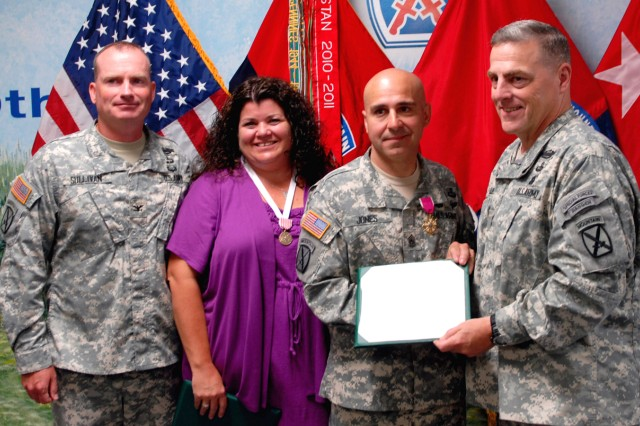 Col. Dennis S. Sullivan, left, 2nd Brigade Combat Team commander, and Maj. Gen. Mark A. Milley, right, Fort Drum and 10th Mountain Division (LI) commander, congratulate Command Sgt. Maj. Benjamin Jones and his wife Leah during an awards ceremony July 18 on Fort Drum. Milley presented the Legion of Merit to the outgoing senior enlisted adviser and the Outstanding Civilian Service Medal to Leah Jones.
