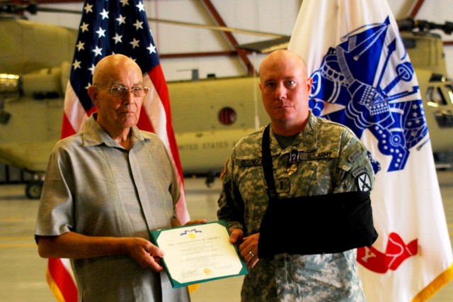 Retired Capt. Gary F. Ossinger, a former OH-6 Cayuse helicopter pilot with 22 years of service, including two Vietnam tours, presents the Army Distinguished Flying Cross his son, Chief Warrant Officer 4 Gary S. Ossinger during a ceremony July 16 at Wheeler-Sack Army Airfield. The younger Ossinger is a CH-47 Chinook pilot who earned the DFC for his courageous actions while bringing reinforcements and supplies under fire to a ground unit that was about to be ambushed. The senior Ossinger earned two DFCs during his tour as a pilot in Vietnam from 1969 to 1979.