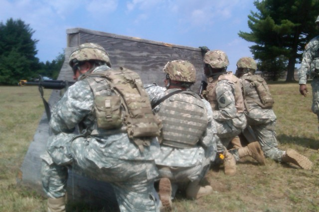 FORT DRUM-- Soldiers assigned to the 101st Expeditionary Signal Battalion negotiate an obstacle during pre-deployment training here on July 22. The unit is preparing to deploy to Afghanistan later this year.
