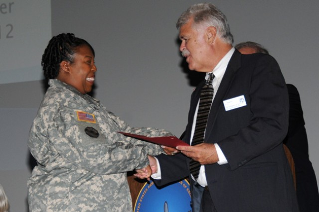 Sgt. 1st Class Claudia Jackson, who earned a Master of Business Administration from Trident University International, receives a certificate of graduation from Grey Edwards, chief of the Army Continuing Education System Hub Fort Benning, Ga., during a graduation recognition ceremony at the post theater July 20.