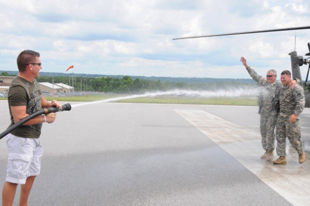 CW5 Lance McElhiney is welcomed with a gush of water on Hanchey field July 20 by his son Lance and joined by his son-in-law Dan, who is a platoon leader stationed at Hanchey field.