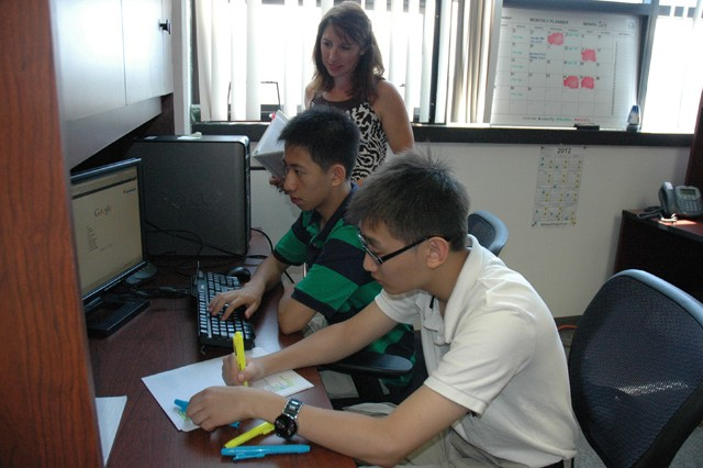 (From left) Gloria Radkiewicz, an information technology specialist from the U.S. Army Signal Network Enterprise Center and on-site mentor, advises to Ben Xu, 15, and Eric Chau, 17, HIRED! apprentices who are working at the USASNEC this summer.