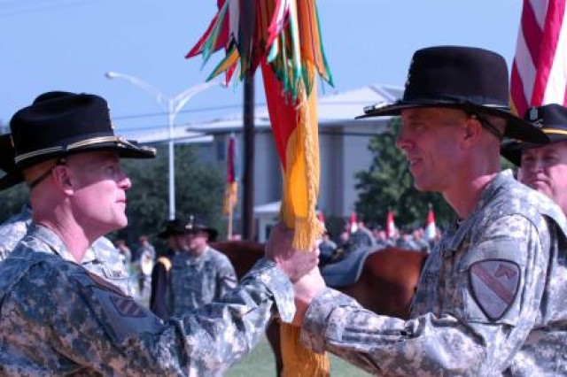 """FORT HOOD, Texas """" Col. Scott Efflandt (right), the outgoing commander of the 1st Brigade Combat Team, surrenders the brigade colors to Brig. Gen. Thomas James (left), 1st Cavalry Division Deputy Commander for Maneuver, during a Change of Command Ceremony here, July 12 at Cooper Field."""