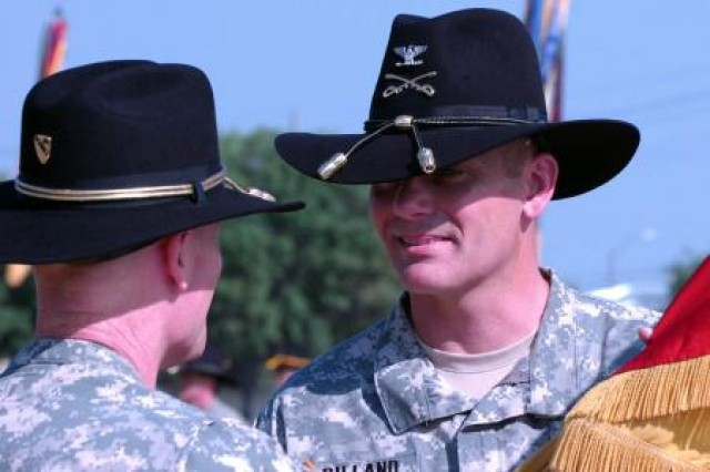 FORT HOOD, Texas - Col. Steve W. Gilland (right), incoming commander of the 1st Brigade Combat Team, receives the brigade colors from Brig. Gen. Thomas James (left), 1st Cavalry Division Deputy Commander for Maneuver, during a Change of Command Ceremony here July 12 at Cooper Field. The ceremony officially marks the beginning of Gilland's command.