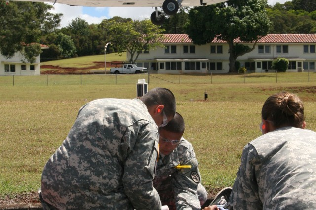 HONOLULU -- Patients received by air transport are evaluated by staff at Tripler Army Medical Center's helipad, July 20, during Operation Chianti, a mass casualty exercise that was coordinated in conjunction with the U.S. Navy's Rim of the Pacific exercise. In addition to air transport, Tripler utilized three ambulance buses and U.S. Army Garrison-Hawaii deployed two Handi-vans for transportation from Ford Island to Health Care Association of Hawaii coalition hospitals.