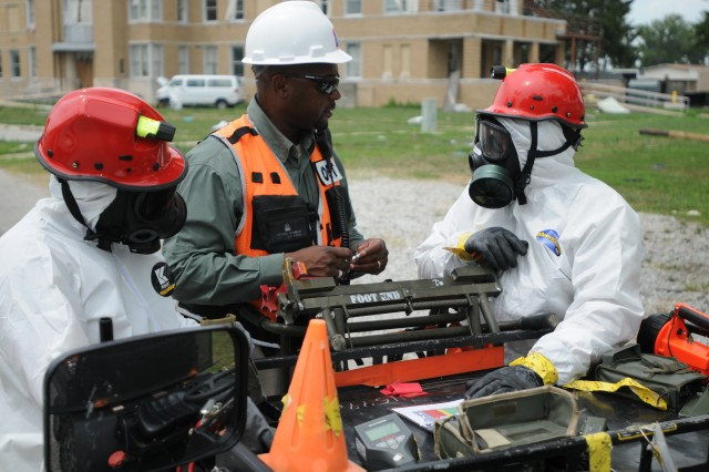 Michael Dunbar, Civil Support Training Activity, U.S. Army North, briefs Staff Sgt. Michael King and Sgt. 1st Class Wendell Reed after the two detected radiation from a nearby parked car at the Muscatatuck Urban Training Center, Ind., as part of Vibrant Response 13, a catastrophic incident exercise conducted by U.S. Northern Command and led by U.S. Army North. King, the survey team chief, and Reed, the chemical, biological, radiological and nuclear noncommissioned officer, both 45th Weapons of Mass Destruction Civil Support Team, Tennessee Army National Guard, were clearing a route to an area hospital for the scenario.