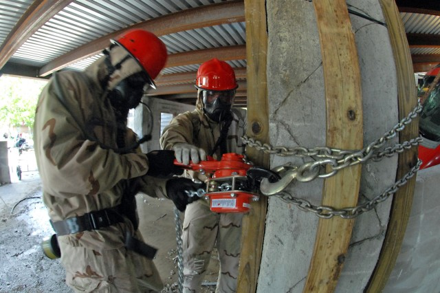 "Engineers assigned to the 178th Engineer Company from Fort Polk, La., apply wooden bracing and linked chains to a pillar supporting a collapsed parking garage July 26, 2012, during a Vibrant Response 13, a major incident exercise conducted by U.S. Northern Command and led by U.S. Army North. During the simulated rescue mission at the Muscatatuck Urban Training Center, Ind., the 178th rescue technicians demonstrated their search and extraction capabilities by treating and evacuating ""survivors"" from the man-made disaster-training venue. After rescuing the role-players, who acted as survivors, the 178th troopers secured the building with bracing so they could safely continue the search for additional personnel."