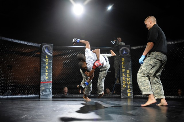Spc. Larry Jackson (red), from Fort Hood, Texas, throws Sgt. Robert Mitchell (blue), from Fort Bragg, N.C., to the ground in the third-place bout of the bantamweight division during the finals of the 2012 U.S. Army Combatives Championship, July 28, 2012, at Fort Hood, Texas. Jackson won the match by judge's decision after three rounds.